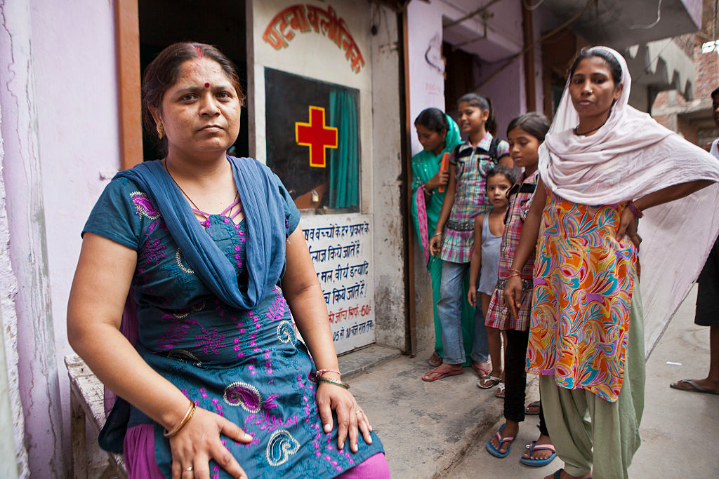 A counsellor sits outside a health clinic as Tuberculosis (TB) patients arrive in Tehkhand Slum, Delhi, India