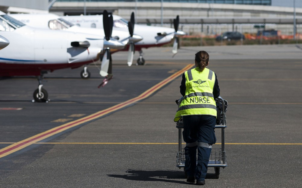 At one of 24 Royal Flying Doctor Service air bases, medical personnel prepare and load equipment on the planes