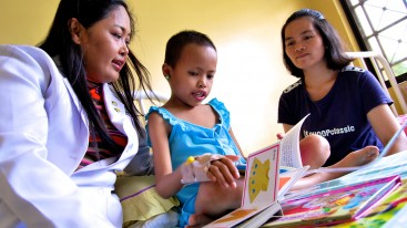 Dr. Mae Dolendo looks at a book with her patient